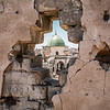 Al Nuri Mosque seen through a wall riddled with bullet impacts - West Mosul