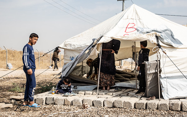 A young men and his family in their newly set up tent in Bardarash camp