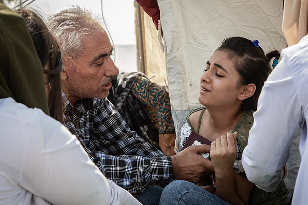 A young girl and her father receiving healthcare in Bardarash camp