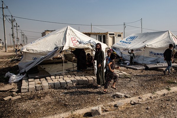 A mother and her children in front of their tent in Bardarash camp