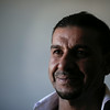 """Ali Yousef, 42,  from Quneitra in Syria stands by the window of the kitchen in an NRC rehabilitated shelter in the Bekaa Valley, Lebanon, on July 23, 2014. <br /> <br /> Ali fled Syria 5 months ago with his wife and 9 children. He told NRC:  """"When things started getting bad in Syria, the company shut down. We left when my wife was 7 months pregnant. I have been trying so hard to find work in Lebanon but I have not succeeded. I am not a carpenter, but I found some work assisting a carpenter. But it dried up after a couple of days. I keep trying. """"<br /> <br /> NRC's rehabilitated shelter programme provides refugees with accommodation by funding owners of partially constructed buildings to complete their properties to a minimum liveable standard. <br /> <br /> NRC/Sam Tarling"""