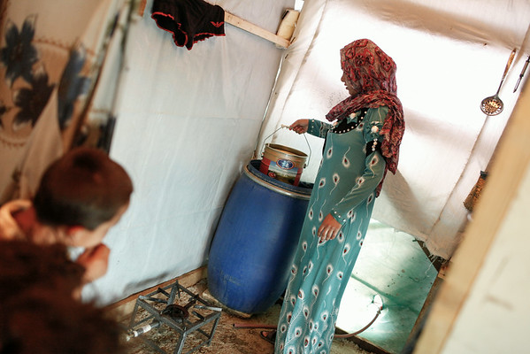 """Rawaa, 21, a mother of three from Aleppo, draws water from a storage tank in her tent at an informal tented settlement for Syrian refugees in the Bekaa Valley, Lebanon, on Thursday July 24, 2014.<br /> <br /> The well is the camp's only water source and is not clean enough to drink. Some residents told NRC that those who drank from the well regularly suffered skin diseases and other complaints.<br /> <br /> Rawaa told NRC:  """"Pulling water up by hand is tough work, especially in Ramadan. These days, by the time I've pulled up a full bucket I'm exhausted. Then I have to take it to my tent in the middle of the camp. There I have to rest, and feed my baby and then bring back the bucket.""""<br /> <br /> Rawaa stores water in a large container in her tent, which she said took 15 trips to fill.<br /> <br /> NRC is running Community Capacity Building projects in the area to ensure community participation, information sharing and coordination of assistance in the ITSs.<br />  <br /> The Community Capacity Building project applies a community based management approach which focuses on the involvement of the refugees in the identification of gaps in services, as well as in the planning and implementing the assistance.<br /> <br /> NRC/Sam Tarling"""