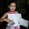 """Sidra, 8, from Ghouta near Damascus, shows certificates of excellence from her school in Syria in a disused store in which her family now live, in the Bekaa Valley, Lebanon, on July 23, 2014. <br /> The family is awaiting placement in an NRC rehabilitated shelter.<br /> <br /> Sidra's mother, Souad, 38, told NRC: """"Sidra loved school. When we left she brought her school books and her school bag with her. When we arrived in Lebanon the first thing she asked me was, Mum, when I am going to start school again? I really hope we will be able to send them next year."""" <br /> <br /> NRC's rehabilitated shelter programme provides refugees with accommodation by funding owners of partially constructed buildings to complete their properties to a minimum liveable standard. <br /> <br /> NRC/Sam Tarling"""