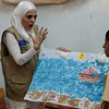 Teacher Rania al Kharaz explains how to make a sea-scene with the help of  Syrian refugees Hamada, 12, and Bayan, 10 (L), at the NRC community centre in Saadnayel, in the Bekaa Valley, Lebanon, on Thursday July 24 2014.<br /> <br /> With Lebanese public schools heavily overwhelmed by the influx of over 1 million refugees since the start of the Syrian crisis in 2011, half of which are children, education programmes such as these provide many young Syrian refugees with education and psycho-social support.<br /> <br /> NRC/ Sam Tarling