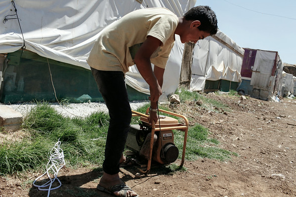"""Ahmed, 15, from Raqqa, starts a generator that gives power to a family's tent at an informal tented settlement for Syrian refugees in the Bekaa Valley, Lebanon, on Thursday July 24, 2014.<br /> <br /> Due to inadequacies in Lebanese power supply, the settlement only receives electricity for two hours a day and few refugees can afford generators or the fuel to run them regularly.<br /> <br /> Suhail, 50, from Raqqa, told NRC that the lack of power made it almost impossible to keep food and made life difficult at night time: """"When the days are shorter we feel like animals: when the sun goes down we go into our homes,"""" he said.<br /> <br /> NRC is running Community Capacity Building projects in the area to ensure community participation, information sharing and coordination of assistance in the ITSs.<br />  <br /> The Community Capacity Building project applies a community based management approach which focuses on the involvement of the refugees in the identification of gaps in services, as well as in the planning and implementing the assistance.<br /> <br /> NRC/Sam Tarling"""