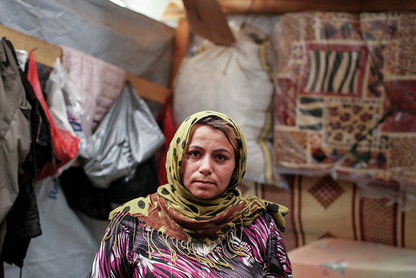 Bouchara, 27, a mother of three from Aleppo province stands inside her tent at an informal tented settlement for Syrian refugees in the Bekaa Valley, Lebanon, on Thursday July 24 2014.<br /> <br /> The camp has no immediate access to potable water, very limited access to electricity and its latrines have not been emptied for five months since being installed by a local donor.<br /> <br /> NRC is running Community Capacity Building projects in the area to ensure community participation, information sharing and coordination of assistance in the ITSs.<br />  <br /> The Community Capacity Building project applies a community based management approach which focuses on the involvement of the refugees in the identification of gaps in services, as well as in the planning and implementing the assistance.<br /> <br /> NRC/Sam Tarling