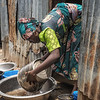 """Fatima Mohammed (20) uses the dirty rain water swept from her home to clean her buckets. """"My home is completely destroyed. My floor has turned to mud and water is everywhere. The rain keeps coming and we do not have any choice but to wait for it to stop or shelter with others."""" Fatima is from the village of Gajibo, just 15kms away from Dikwa. """"The armed groups came and destroyed our village. I really want to return there one day because it is not far but I am too scared,"""" she said. Most of the village´s inhabitants live in Fulatari camp."""