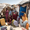 """Mohamed Adulaihi, 35, and his wife, Mumina Ahmed, 25, his mother (yellow) and five children sit in front of their shelter in an settlement for displaced families in Kismayo, a coastal town in South Central Somalia. <br /> <br /> The family fled Barawe in the Lower Shabelle region in February 2018 due to the drought and to seek treatment for Mohamed's illness. """"I am not sure what the problem with my stomach is"""", he says. """"It is swollen and feels sore. I had some fluids removed, and now it feels a bit better sometimes.""""<br /> <br /> Due to his illness, Mohamed is not able to work, so his wife Mumina is now the family's breadwinner. She transports materials at construction sites for a daily rate of 5-6 US dollars. The family has not yet received aid since they arrived here. Materials for their makeshift shelter were provided by their neighbours. NRC is helping some communities in Kismayo, but more aid is needed to help more families. <br /> Date: February, 2018<br /> Photo: NRC/EU Christian Jepsen"""