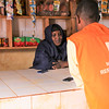 NRC staff talk with Mariam about the sucess of her store since moving it out of her home and into the community market. Photo: Adam Omar/NRC