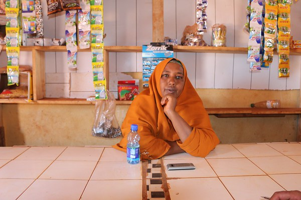 Mariam Hussein, a 38 year old mother of eight poses for the camera in front of her new store in the community market. Photo: NRC