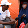 An NRC staff speaks with Asha Hussein (35). She is a mother of four children, aged between four and ten years. She has been living in a shelter camp in the outskirts of Mogadishu. She used to live in in the Lower Shabelle Region, cultivating a one-hectare farm as well as keeping domestic animals. But the drought in 2017 took away all her animals, 15 cows and 20 goats. They all died from starvation. Her crops dried up and died. Water became scarce. Boreholes and wells dried up. All her survival options dwindled, and she could not stay in the village any longer. <br /> <br /> In Mogadishu, she lives in a tent house and survived on a cash program that enables her to afford basic necessities from the local market. Photo: NRC/Nashon Tado, 2017