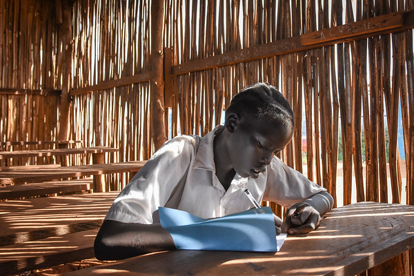 """Nanyan (14) has just received her exam results and was best in class. """"I knew the test went very well,"""" she smiles.  """"I want to become a nurse. That´s why I need to study hard.""""<br /> """"I want teachers who can teach us well, so that we can learn and become good people in the future"""".<br /> She fled Bentiu in 2016 and has since then lived in a protection of civilians site in Juba. <br /> """"Life here is hard because we lack a lot of things, like sufficient water and food. Before, outside here, we had enough. Outside life was very good. We had enough to eat ad I was living in a proper house.""""<br /> """"I want to be able to help my parents in the future"""".<br /> """"I want the country to be in peace, so that we can return back home. I want the country to be okay"""".<br /> <br /> NRC's education projects in the protection of civilians sites in Juba are funded by UNICEF. This photo is from Hope primary school in POC3. The school has more than 3000 students from 1st to 8th grade and is running two shifts a day.  <br /> Photo: Norwegian Refugee Council/Tiril Skarstein"""
