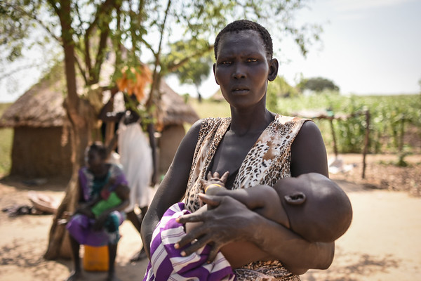 """Khot Dau (30) and her three months old baby named Dau, after his grandfather.<br /> Khot has three children. <br /> She is receiving food aid from NRC as part of a food distribution financed by WFP. Photo: NRC/Tiril Skarstein<br /> <br /> Quotes:<br /> """"What I eat is food, that´s what I eat. I eat sorghum. <br /> I eat twice a day.<br /> We eat from what we grow. Like now we have grains, beans, groundnuts and okra – and I can get them and cook.  <br /> <br /> I cook food for the children. Like now, when we have grain. <br /> The challenge is during the dry season, then I have nothing, only grains. <br /> If it is rainy season, I grow food. This is my livelihood. <br /> When it is the dry season, like now, I get more challenges. With the vegetables I grow, I can buy soap and anything from town. And when there is no vegetable, during the dry season, that is when I get many challenges. Because I am taking care of children. <br /> How I will help my children is to take them to the swampy area, so that I can grow vegetables. And if I have a fishing net, I will put it in the river."""""""