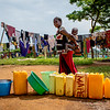 A Congolese refugee carrying her child walks past a line of jerrycans and other water containers for refugees waiting for clean water. With little aid funding, there's not enough clean water for all the new arriving refugees at the Kagoma Reception Centre. Risks of waterborne diseases are rising. Around 4,500 Congolese refugees are currently staying here, waiting to receive shelter and household items. The conditions in the centre are difficult and extremely overcrowded. Chronic underfunding of the Congolese refugee response has led to many gaps in emergency assistance.<br /> Credit: Dwyer/NRC <br /> June, 2019
