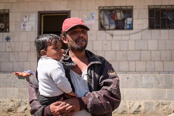 """Adnan Hassan Ali, displaced from Hodeida, with his six-months-old son Hassan. They have just arrived to this school in Amran where they are living with other families.<br /> <br /> """"I fled from Hodeida. My house was hit from the air. We escaped to Amran into this school. We had explosives falling on our houses, shrapnel falling on us, shrapnel reached our house. We were very scared, and we hid under the chairs just to be protected. We expected the war to get worse, and that's why we escaped, before things got more complicated, before we all died.<br /> """"We went where others advised us to go, where there were a lot of displaced people. We came to Amran, but when we reached Amran we couldn't find a place to stay, so we ended up in this school. We lack everything here. We lack medicines for children, diapers and other stuff. No food items, nothing.<br /> """"This is a poor kid, we are displaced. I want to talk on behalf of the displaced here in this school: We're exhausted, we really are. We had to come here against our wishes and we're in a bad state. We'd love to go back to our homes but there's nothing left of them. <br /> """"We need more aid and more support … look what conditions we're living in. We've been forced into this, with no water, rice or sugar. We have nothing here, we beg our neighbours for food. We go to the pharmacy looking for medicine and they ask us for money. We have no money. They tell us you have humanitarian organisations helping you. They think that whatever we get form aid agencies will never end.""""<br /> <br /> Photo and text: Karl Schembri/NRC<br /> Photo taken on 28 January, 2019"""