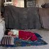 Young boy sleeps in IDP camp in Kabul