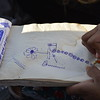 A student not having notebook writing on corn store bill at the Camp Adha high school. Photo: NRC/Enayatullah Azad, Nangarhar