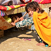 Sharmila, 6, is Abdullah's sister and pushing his sleeping bag to put him to sleep. Sharmila is not going to school, instead, she brings water from the nearby village well and pushes Abdullah's sleeping bag every day.  <br /> Photo: NRC/Enayatullah Azad