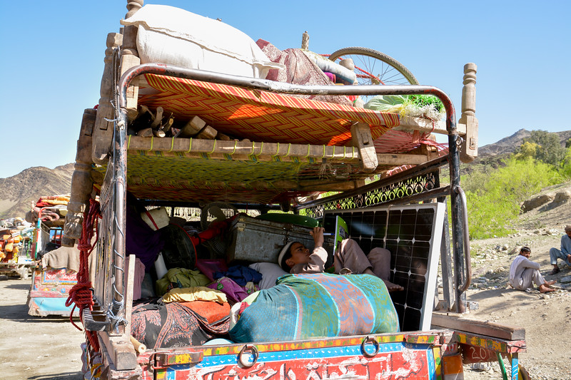 Rafiullah, 13, sitting inside a small truck taking care of the family's belongings at the Torkham crossing. His family has gone to register themselves with DoRR. The family has just crossed the Torkham border and reached into Afghanistan. <br /> Rafiullah's father, Rostam, 32, though was born in Pakistan, but they weren't registered as refugees in Pakistan. They were living in Miskin Camp, Khyber Pakhtunkhwa. Rafiullah's family is originally from Laghman province in Afghanistan but now, the family has no idea where to go. <br /> Photo: NRC/Enayatullah Azad