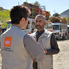 NRC head of program, William Carter and area manager for east Rahimgul Amin at Torkham Border. Trucks carrying unregistered Afghan returnees belonging are in the background. <br /> Photo: NRC/Enayatullah Azad