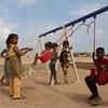 "Alofa from Mahra (yellow dress and trousers). ""I was afraid in Yemen. I am happy now."" The boy in the red shirt is called Dawood, and the little by on the swing is called Saed (2)."