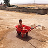 The son of a displaced family from Sinjar is cooling down in a wheelbarrow because of the intense heat (52 degrees celsius). In Dohuk, Iraq, August 2015. Photo: NRC/Hussen Alnabe