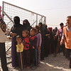 Newly displaced Iraqi families queue at a distribution point in Debaga camp where NRC provides water, food parcels, hygiene and baby kits. The camp currently hosts more than 6,000 families who have fled their homes in Mosul, surrounding cities and elsewhere. <br /> <br /> Photo: Karl Schembri/NRC