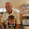 """Ahmed and his 4 year old son Hesham. <br /> <br /> Ahmed (56) is originally from the village of Haji Ali outside of Makhmour southeast of Mosul, but when he was forced to flee his home, he ended up in Debaga camp. <br /> He fled with his wife and seven children 25 days ago on the 12 June 2016 because of the dire situation with no food, no water and no electricity and under constant fear of armed opposition groups.  <br /> """"When the airstrikes started, the situation got very bad. We were stuck in the middle of the fighting and no one dared to leave their houses anymore,"""" Ahmed says. """"ISIS were mining all exits routes so no one could escape and they would kill anyone they thought would attempt to leave"""". <br /> Ahmed and his family survived on their own crops. """"Salares ware no longer being paid and not many products were left in the shops, the few products that one could buy were heavily priced. We survived on our own crops although ISIS would take their own share"""". <br /> Ahmed tells us that children stopped going to school when ISIS changed the curriculum after taking control of the area in 2014: """"The children would go to school and learn about violence and war so we decided to pull them out of school,"""" Ahmed said.<br /> When the Iraqi military launched their offensive to retake Makhmour and the surrounding villages, Ahmed and his family were caught in the fighting. They decided to try to make a run for it. <br /> """"During nighttime on 12 June, we started walking towards the direction of the Iraqi military forces' positions raising white flags  so they wouldn't shoot at us. We were only carrying our ID cards and the clothes we were wearing. That is all we took with us. The valley was protecting us from snipers and the bombings and we finally made it to the Iraqi military forces. They drove us to Debaga camp in their vehicles,"""" Ahmed says.  <br /> """"The humanitarian organizations are doing their best to support us, but we need to go home,"""" Ahmed says. <br /> <br /> Pho"""