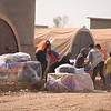 Newly displaced families from Tub Zawa carrying emergency aid in Khazar Camp, Hasan SHam.<br /> Over 1,000 people fled their village overnight as Iraqi forces advanced towards Mosul city.<br /> NRC delivered emergency supplies including food, water, hygiene kits and baby supplies.<br /> Photo: Karl Schembri/NRC
