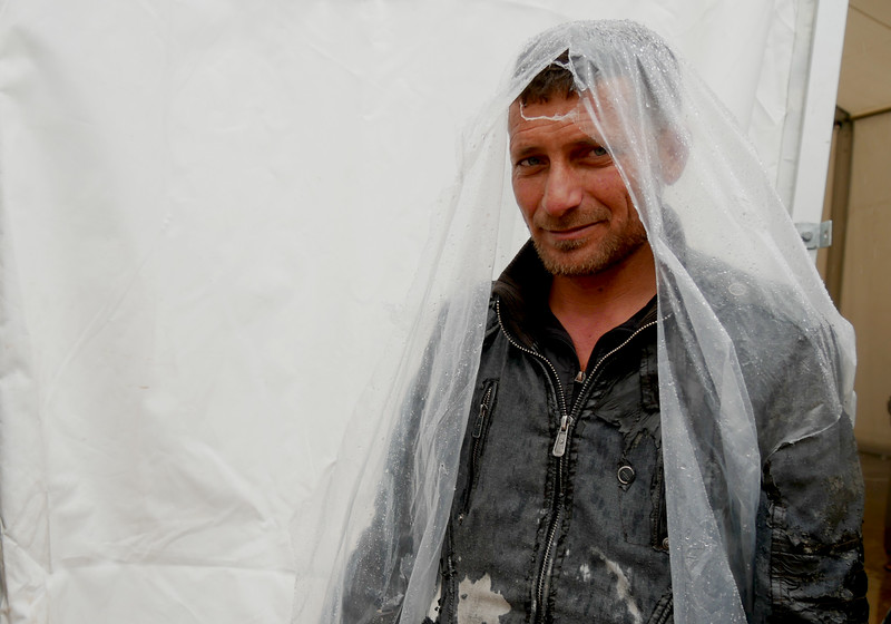"Abid Abdulla (38), originally from Mosul has been recently displaced patiently waits in a the queue to get food and water. <br /> ""It is rainy and cold, but I have four children who need these items,"" Abid says. ""I am really thankful for NRC for providing us these necessary items,"" he says. <br /> <br /> Date: 16 March 2017<br /> Photo: Sarhang Sherwany"