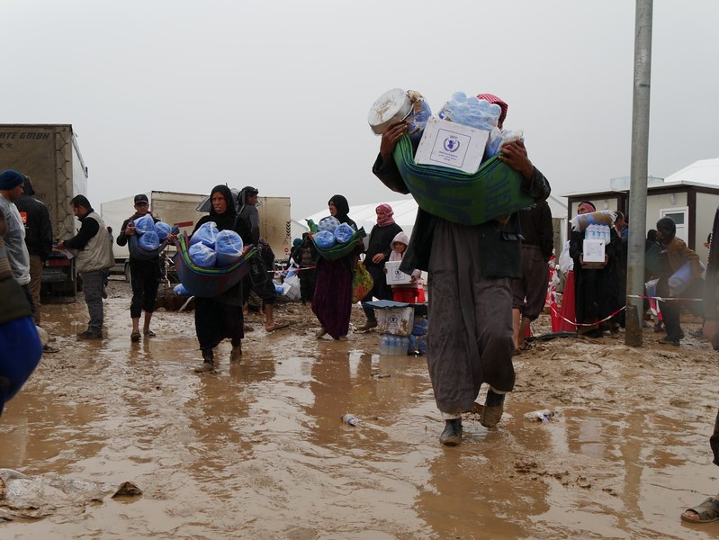 A man carries food and water distributed by NRC a reception centre for people who have fled Mosul.<br /> <br /> Date:16 March 2017<br /> Photo: Sarhang Sherwany/NRC