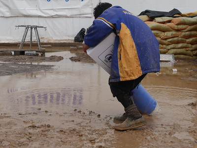Rain has made this difficult for this boy carrying supplies that have been provided to him by aid agencies in a camp for displaced people near Mosul.  Date:16 March 2017 Photo: Sarhang Sherwany/NRC