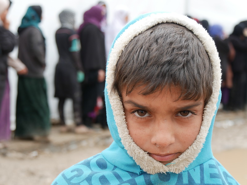 """Ahmed Rashed (7) from Mosul who has recently been displaced to Hamam al-Alil. """"When I grow up, I want to be a teacher,"""" Ahmed says.<br /> """"I want my children to go to school, and have safety and joy,"""" Ahmed's mother says while waiting in a line to receive blankets, water, and hygiene kits from NRC.<br /> <br /> Date: 16 March 2017<br /> photo: Sarhang Sherwany/NRC"""