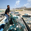 """Wafdi Suhail Baker, 25, from Shatee Refugee Camp and father of two, stands on his destroyed boat which used to provide his family with their livelihoods. <br /> """"We're a family of fishermen and this was my boat on which I used to work together with my father and brothers,"""" Wafdi said. """"In the last war my boat together with seven others belonging to our relatives were bombed while they were berthed in Gaza Harbour. All the nets, engines, and equipment were gone; not even the fire fighters could reach the port as it was too dangerous. We're now working for other fishermen making only a fraction of the income we used to make when we had our boats. It's humiliating."""" <br /> Photo: Karl Schembri/NRC"""