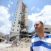 """Hazem Zaqout, 43, his mother and brother owned three apartments in the 16-floor Italian Complex in Gaza City. The complex was destroyed on 25 August last year, in the final hours of the 51-day escalation, rendering some 60 families homeless and destroying dozens of shops at the street level.<br /> Weeks before the complex was destroyed, Hazem's brother, Ahed, who lived in the same tower, suffered a direct hit from an Israeli missile that killed him immediately. Ahed was a coach for the Palestinian children's football team which participated in the Norwegian Peace League in the mid-nineties.<br /> """"We lost our home, my life savings, and my brother in the last war,"""" Hazem says. """"On 25 August around 11pm I received a call from the Israeli military telling me to get out of the building in 10 minutes. I begged them to give us more time, everyone was asleep, people were fleeing in their underwear. I couldn't believe they would do this to us.""""<br /> Hazem and his brother were still paying their loans for the flats they bought around 10 years ago. Now he is living with his family and mother in two rooms they are renting from a relative.<br /> """"I'm sick of living here,"""" Hazem added. """"Who will take care of my three children if I get killed? How will I protect them when the next war happens? I want to leave Gaza and live somewhere safe for my children.""""<br /> Photo: Karl Schembri/NRC"""
