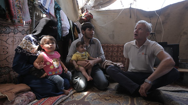 NRC Secretary General Jan Egeland with Thaer Al Sheesh (left), 30, father of three girls and a four-months-old boy, from Beit Lahiya, had his house destroyed in the last war almost three years ago. He is still living in a tent with his 53-year-old mother, Intisar, and his family, as they wait for their house to be rebuilt. His baby was recently attacked by a dog which entered their tent at night.<br /> <br /> Photo: Ahmad Mashharawi/NRC<br /> 5 June, 2017