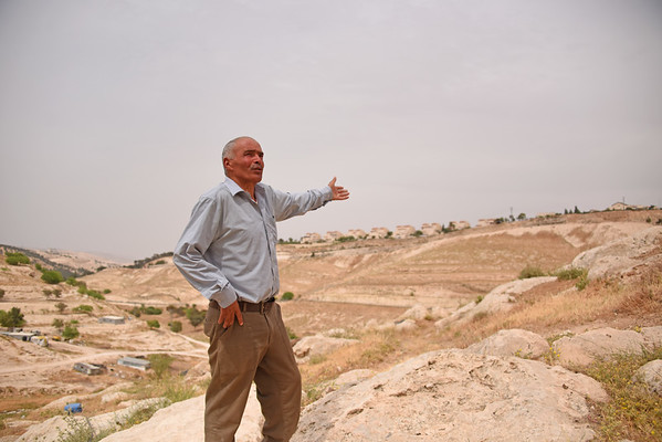 """Background: In Wadi Al Jimel, a community of Palestinian Bedouin refugees from Beer Sheva is facing the threat of forced eviction, home demolitions and continuous settler violence from the nearby settlement of Maale Adumim. The community is located in Area C, under full Israeli security and administrative control. The community is at risk of forcible transfer due to a """"relocation"""" plan located in the area advanced by the Israeli authorities. The community exists in a high security area, movement restrictions are imposed to people when transporting on bypass road, and when herders graze their animals in access restricted areas near the settlement and the wall. In 2002, the community was separated from Jerusalem area by the separation wall.<br /> <br /> Moussa Al Sayayleh<br /> We've been living here in Wadi Al Jimel since 1983. We started with a small group and we grew to the numbers you see now. We have 28 or 30 families here, each consists of six or seven persons and more in some families. We face many problems from the civil management due to the expulsion, the wall and the street that will be closed now. <br /> The life of Bedouins here is not different from the one of Bedouins in Saudi Arabia or Jordan or Palestine. Bedouins rely on livestock and they move with them in order to raise them and to find water. Wherever it is convenient for them and their livestock, they remain there. Traveling and moving doesn't bother them. But we have been suffering from expulsion, confiscation and settlements ever since Israel came into being and occupied the land and kicked the Bedouins out. Bedouins in Palestine now do not dare leave the place they've staying in for 10 or 50 years, because if they do so, they will not be able to return to it. So their life has become a sedentary one because they are obliged to stay in their own area and not to travel. The Bedouins' life was way better before than it is now. They used to go to whichever place they wanted and live where it was s"""