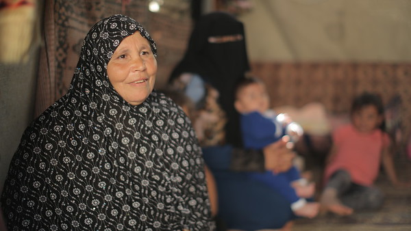 Intisar Al Sheesh is Thaer's mother, living with him and his family in a tent, three years since their house was destroyed in the last war on Gaza<br /> <br /> My name is Intisar Al Sheesh. I am 53 years old. I got married at the age of 18 and I gave birth to nine children. Our family consists of 11 members. My husband first started working in Israel, then he lost his job when Israel imposed a blockade and stopped Palestinians from Gaza from going to Israel. <br /> <br /> In the last war, we got displaced and stayed in schools. We couldn't find food or water or anything. We took refuge in schools for fear of the planes flying above us and artillery shooting at us. After that, we searched for a place to stay in and ended up renting one. My children stayed with their cousins. Later, we couldn't pay the rent so we had to build the tents that you see now. We are living in these tents in horror and fear because of the dogs, ants and snakes that come to us. <br /> <br /> We waited for the construction to start for three years now and still it hasn't started yet. We are still living inside these tents and it is not a decent life. The Israelis imposed a blockade on us and we are not receiving any assistance. They cut off the electricity and there is no work for us. As you can see, everyone is sitting down doing nothing. There is no income. We hope a house will be built for us so we live inside like normal people and own things like everybody else. We hope the blockade is ended and peace prevails, so these children can grow up and work too.<br /> <br /> Photo: Ahmad Mashharawi/NRC<br /> 4 May, 2017