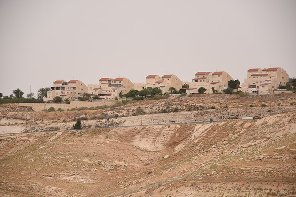 """The settlement of Maale Adumim surrounds the community of Wadi Al Jimel, where a community of Palestinian Bedouin refugees from Beer Sheva is facing the threat of forced eviction, home demolitions and continuous settler violence from the nearby settlement. <br /> The community is located in Area C, under full Israeli security and administrative control. The community is at risk of forcible transfer due to a """"relocation"""" plan located in the area advanced by the Israeli authorities. The community exists in a high security area, movement restrictions are imposed to people when transporting on bypass road, and when herders graze their animals in access restricted areas near the settlement and the wall. In 2002, the community was separated from Jerusalem area by the separation wall.<br /> <br /> Photo: Karl Schembri/NRC"""