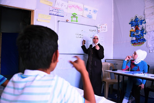 "Warda, a mother of three children, teaches Arabic and Maths at this centre in Sahnaia on the outskirts of Damascus, Syria. <br /> <br /> Warda said: ""A lot of the displaced children have dropped out of school, some of them for years, so it's hard for them to catch up on their education. Many of them have to work because there are no other breadwinners in their families. Having had to flee their houses affects them in so many ways. <br /> <br /> ""I love coming here to teach because, as a mother, I know how important education is for my children.""<br /> <br /> Supported by NRC, the centre is run by a community-based association which assists around 150 displaced children from across Syria and others from the community catch up on their education. The centre runs catch-up classes for children and hosts recreational and life skills activities through its Summer Programme for children who have been out of school because of the crisis and displacement. Children are prepared to pass government-recognised exams in Arabic, Maths and English so they can eventually return to formal schools.  NRC also helps to facilitate a vital link between this community-based initiative and the Ministry of Education.  <br /> <br /> NRC has been supporting the centre since June 2016, providing student backpacks and supplies, teaching materials, teacher training, and providing administrative support to the association.  <br /> <br /> Photo: Karl Schembri/NRC<br /> 24 August 2016"