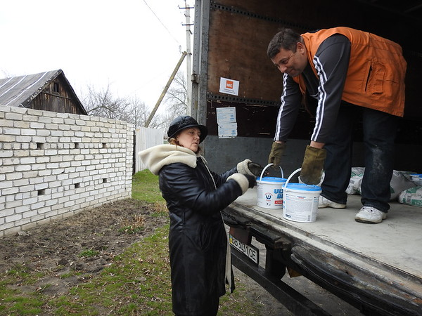 Olga receiving construction materials to repair her damaged house