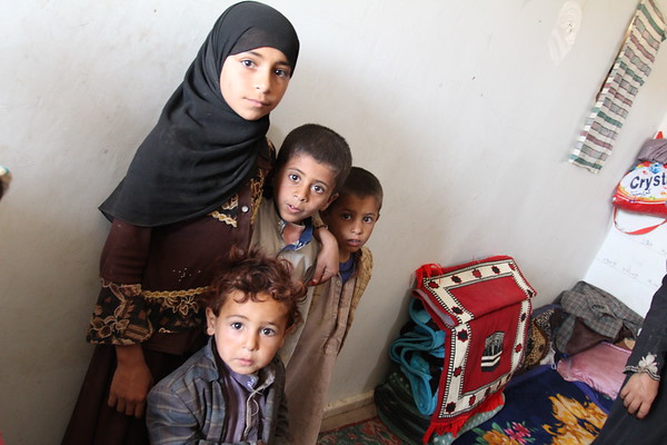 """Father: Ali. Mother: Ghazal. 5 children here: Ramz (12), Tareq (8), Riyad (7), Haytham (2) baby Zahra (4 months). Grandmother: Jeida. <br /> <br /> Two families live in two separate rooms at the school, while the rest of the school still operates for the local kids, and the kids of the two families. <br /> <br /> Ali: <br /> """"I used to have a workshop where I fixed cars, but it was hit by an airstrike. We lost everything. An airstrike also hit close to our home, and damaged our house, we could not stay there.""""<br /> <br /> """"We fled in a car, it was twenty of us, all in one car."""" """"People in this village were so kind and let us stay here"""" <br /> <br /> """"We don't want to stay in a settlement, it is shameful. My sister has a mental illness, she needs special care, we need to look after her""""<br /> <br /> """"If the airstrikes stop, definitely we will go back"""" <br /> <br /> """"When we hear the jets over us, even here, we get scared, as they might hit the school""""<br /> <br /> """"My mentally ill sister's situation was better before, but now, after the airstrikes, she has become unable to restrain natural discharges. She needs a lot of special care.""""<br /> <br /> """"We were in a good situation, we did not need anything, now we cannot do anything."""" <br /> <br /> """"I go and work at the khat farms, my bother-in-law repairs cars, I help him, and we got some blankets and other things we need from NRC.""""<br /> <br /> <br /> Ghazal: <br /> """"We had everything we needed, a house, everything, now we all live together in this small room."""" <br /> <br /> """"It was hard to have this baby under these circumstances""""<br /> <br /> Photo: NRC/Alvhild Stromme"""