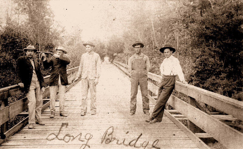 William Richmond Stewart, left, other men, unknown, on the original Long Bridge wood crossing bridge, Adel Highway (Identifications requested - berriencountyga@alltel.net)