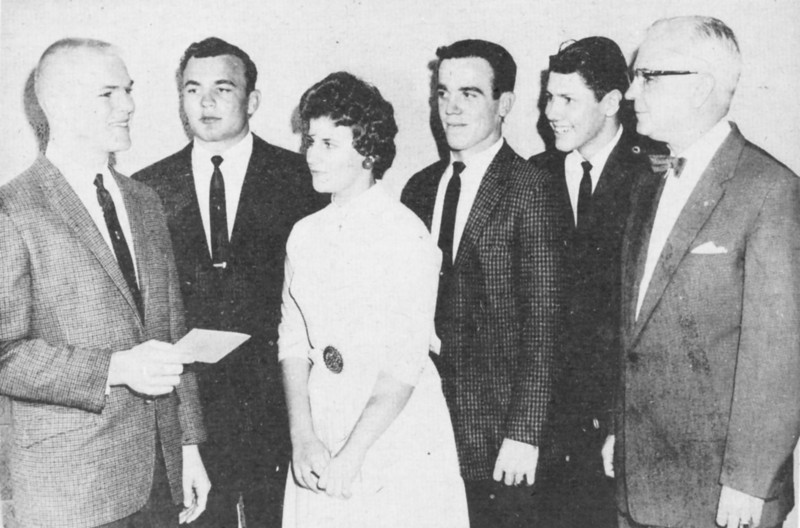 First Annual Leadership Banquet, February, 1962. Johnny Akins, chairman of the program for the first annual   leadership banquet, talks over the events for the evening with others on the program, left to right: Elliott Garner, Judy Rowe, Butch Alexander, Billy Bob Nix, and George Schlegel, speaker for the evening.