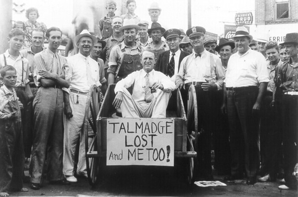 he Nashville Herald, front page, September 17, 1936<br /> GIVEN ELECTION VICTORY RIDE HERE LAST THURSDAY<br />      The boys had fun over results of the election last Thursday afternoon.  Above is shown Mark Sutton, a Talmadge support, just before riding Howell Giddens, a Russell supporter, to the Georgia & Florida depot and back in a push cart, the fulfillment of an agreement between the two prior to the election.  Seated in the cart is Mr. Giddens, while from left to right are Reuben Sumner, Mayor J.V. Talley, Mark Sutton, (the loser), Night Police J.C. Gay, Chief of Police J.B. Frost and Deputy Sheriff J. Wesley Griner.  Picture by Pat Sullivan, local photographer. (Byline courtesy of Skeeter Parker)