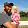 Watching them drop some cover seed at Hollis Hill Farm on Thursday is owner of the farm Jim Lattanzi and his daughter Emilyn, 2. SENTINEL & ENTERPRISE/JOHN LOVE