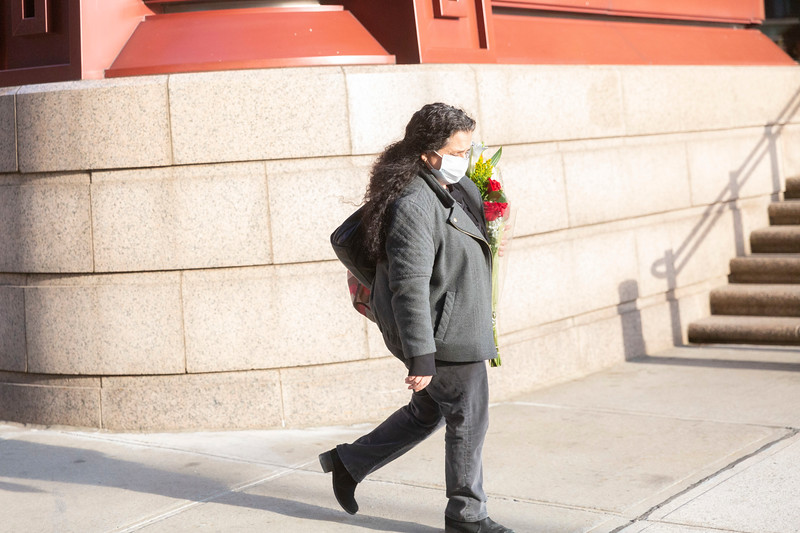 NEW YORK - March 24, 2020: for NEWS. A woman walking on Water street wearing a mask and carrying flowers to the Staten Island Ferry amid the COVID-19 Coronavirus pandemic. nypostinhouse (Photo by: Taidgh Barron/NY Post)