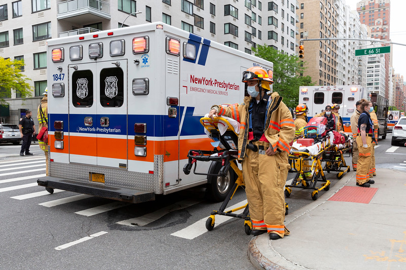 NEW YORK - May 18, 2020: for NEWS. New York Presbyterian EMS personal wearing PPE and masks (unsure of if EMTs or Paramedics) stage at a high rise fire at East 66th Street and 3rd Avenue in the Upper East Side amid the COVID-19 coronavirus pandemic.  nypostinhouse (Photo by: Taidgh Barron/NY Post)