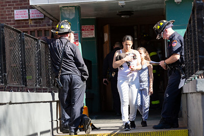 NEW YORK - March 9, 2020: for NEWS. Evacuated residents leave with their puppy from an apartment fire in NYCHA King Towers in Harlem off Lenox Avenue. (Photo by: Taidgh Barron/NY Post)