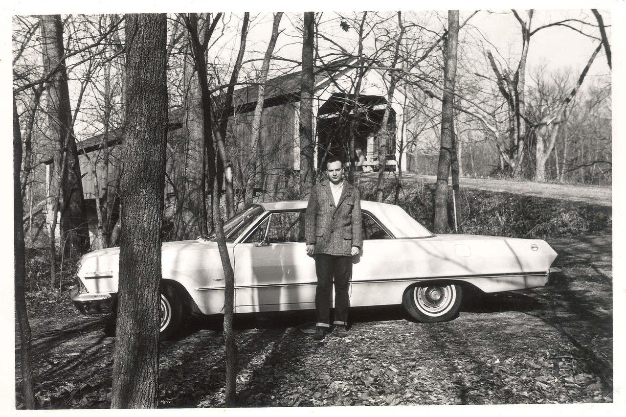 This is a photo from my family album.  It is my dad in front of what I believe was the Parke County Red Covered Bridge near Rosedale, Indiana.  My grandma was raised on a farm just down the road from the Red Bridge.